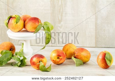 Many Juicy Beautiful Amazing Nice Peaches On Light Wooden Background. Beautiful Food Art Background.