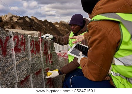 Side View Portrait Of Two Industrial Workers Wearing Reflective Jacket Marking Piece Of Granite On M