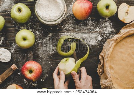 Cooking Apple Pie. Hands Peeling Apples For Apple Pie On The Wooden Table. Top View