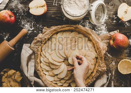 Cooking Apple Pie. Hands Adding Apple Slices To Pie Crust. Apple Pie Ingredients On Wooden Table