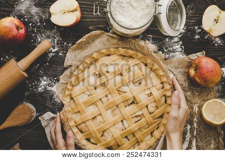 Cooking Apple Pie. Hands Holding Apple Pie Ready To Be Baked. Apple Pie Ingredients On Wooden Table