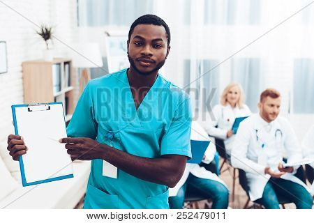 Black Doctor Holding A Sheet Of Paper. Multinational Medician Consultation. Medical Teamwork Connect