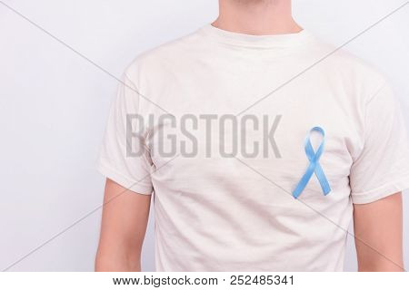 Oncological Disease Concept. Man Wearing White T-shirt With The Light Blue Ribbon As A Symbol Of Pro