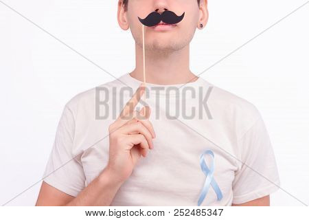 Oncological disease concept. Man with decorated moustache wearing white t-shirt with the light blue ribbon as a symbol of prostate cancer pinned on the side of heart. poster