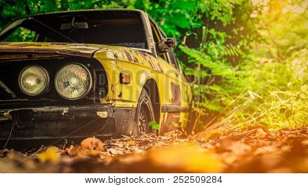 Old Wrecked Car In Vintage Style. Abandoned Rusty Yellow Car In The Forest. Closeup Front View Headl