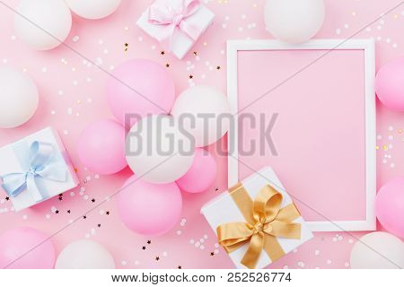 Birthday Mockup With Frame, Gift Box, Pastel Balloons And Confetti On Pink Table Top View. Flat Lay
