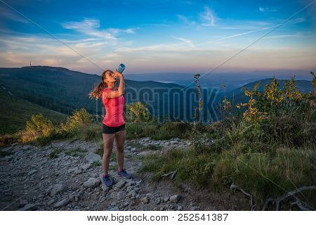 Thirsty woman trail runner drinking water from water bottle. Szczyrk, Beskidy Mountains, Poland poster