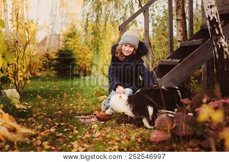 Autumn Portrait Of Happy Kid Girl Playing With Her Spaniel Dog In The Garden, Sitting On Wooden Stai