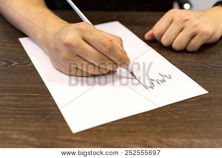 Man Sitting At Table And Holds Pen In His Hand. There Are Sheet Of Paper With A Trading Chart On The