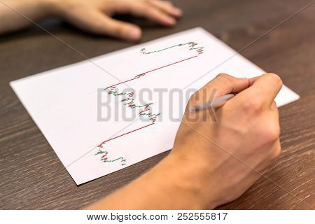 Man Sitting At Table. There Are Sheet Of Paper With A Trading Chart On The Table. Concept Photo.