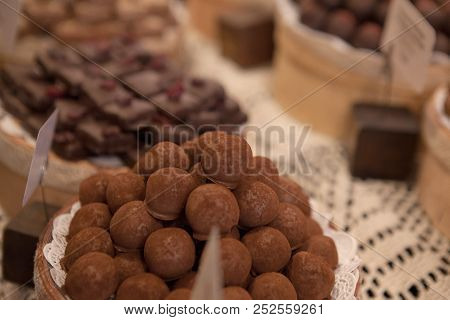 Asorted chocolate truffles and pralines. Chocolate and coconut candies on the counter in the confectionery store poster