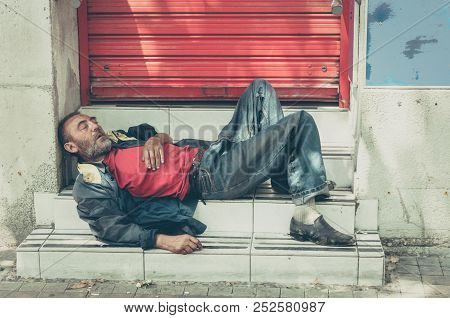 Homeless Man. Poor Homeless Man Or Refugee Sleeping On The Stairs On The Street, Social Documentary