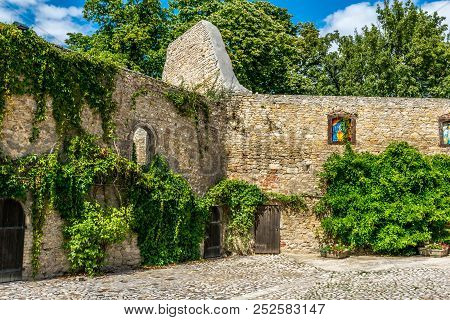 Old Stone Wall From A Castle Ruin Which Is Overgrown By Green Ivy And Other Plants. Cobblestone In T