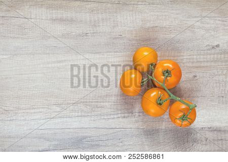 Branch Yellow Tomatoes On Light Wooden Surface.