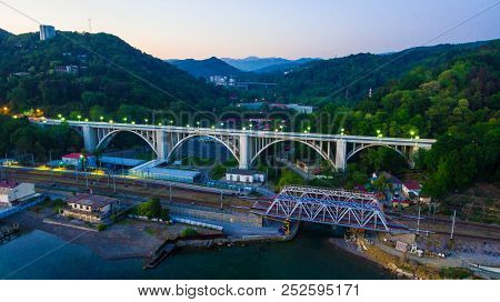 Drone View Of The Illuminated Matsesta Viaduct And Railway Bridge On The Background Of Mountainsides