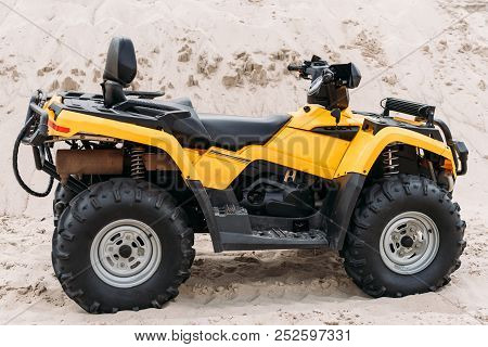 Side View Of Modern Yellow All-terrain Vehicle Standing In Desert On Cloudy Day