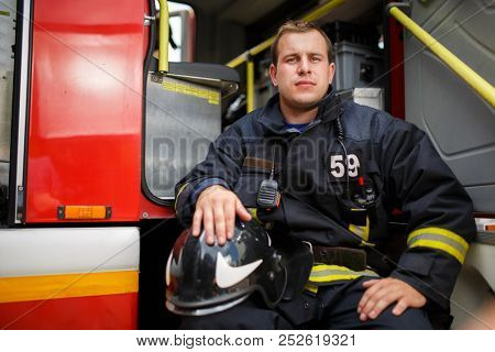 Photo of fireman sitting in fire truck