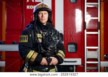 Photo of fireman wearing helmet with gas mask on background of fire engine with stair at station