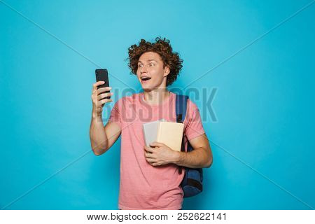 Image of attractive youngster guy with curly hair wearing casual clothing and backpack holding smartphone and books isolated over blue background