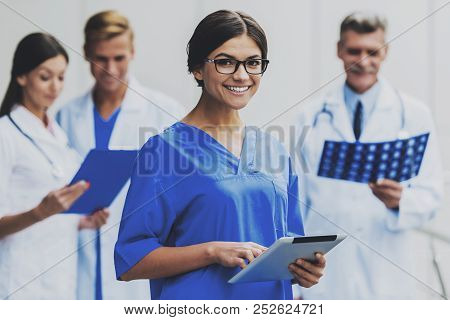 Smiling Woman Nurse Portrait.. Clinic On Background. Famale Doctor. Group Doctors In Clinic. Healthc