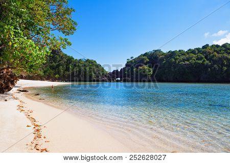 Kid Relaxing On Desert White Sand Beach After Trekking In Tropical Jungle To Segara Anakan Lagoon Wi