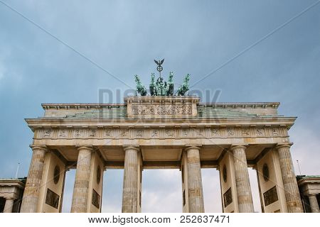 Brandenburg Gate In Berlin Gainst The Backdrop Of The Setting Sun In The Evening. Architectural Monu
