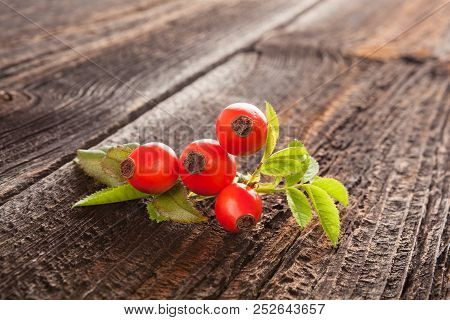 Fresh Red Rose Hips With Green Leaves On Wooden Background. Immunity And Vitamin Plant.