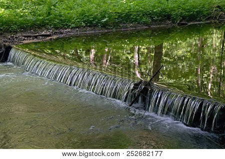 Brook Water Cascading Over A Weir In Forest