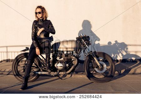 Sexy biker young woman in black trendy leather jacket sit on vintage custom made caferacer motorcycl