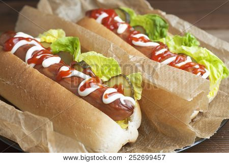 Two Homemade Hot Dogs With Mayonnaise, Ketchup, And Green Letuce Leaves Decorated With Baking Paper,