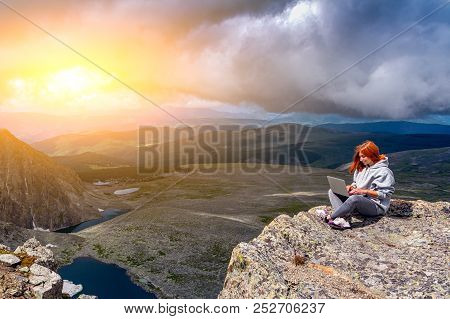 Young Tourist Woman Working On A Laptop And Sitting On The Top Of The Mounting And Looking At A Beau