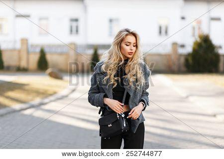 Beautiful Young Stylish Woman Model With A Stylish Black Handbag In A Gray Fashion Coat Posing Outdo