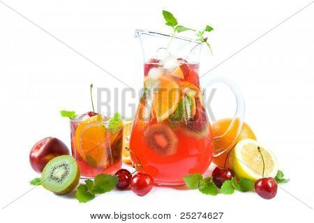 Jug and a drinking glass with colorful summer punch or lemonade and fruits.