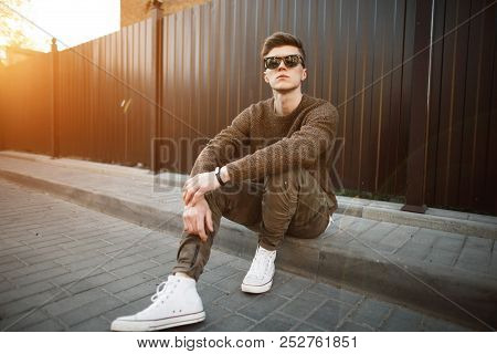 Handsome Fashion Hipster Man In Stylish Sunglasses In A Fashionable Pullover And Military Stylish Pa