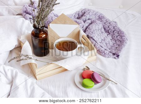 Morning Breakfast In Bed Wooden Tray With A Cup Of Tea, Sweet Colorful French Macaroons, Love Letter