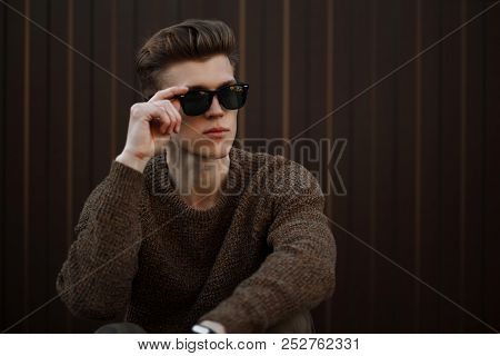 Fashionable Hipster Man With Sunglasses And Fashionable Clothes With White Sneakers Sitting On The S