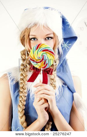 Pretty snow maiden holding bright lollipop looking in camera