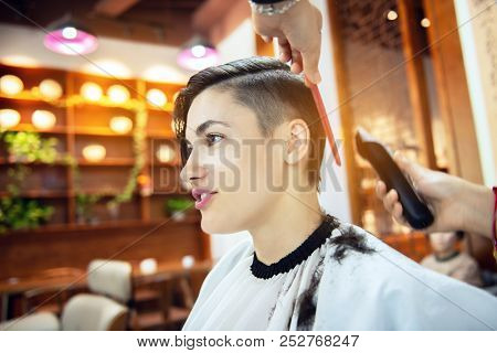 Beauty, hairstyle, treatment, hair care concept, young woman and hairdresser cutting hair at hairdressing salon. Hairdresser cuts beautiful girl's hair. Hairstylist serving client at barber shop.  poster