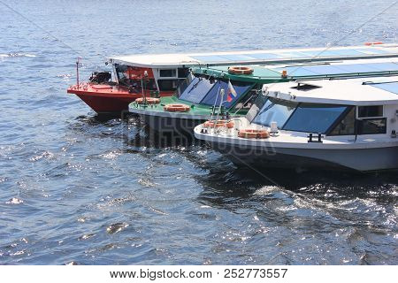 Three Excursion And Tour Cruise Boats Moored On River Water. Cruise Ships With Passengers For Guided
