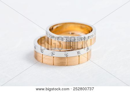 Two-tone Wedding Rings With Diamonds On White Background. Rose Gold And Silver Rings For Bride And G