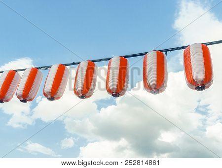 Paper Red-white Japanese Lanterns Chochin Hanging On Blue Sky Background