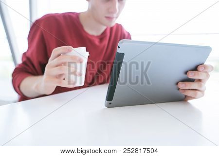 Young Man Sitting At A Table In A Red Sweatshirt With A Tablet And A Glass Of Coffee And Hands. Stud
