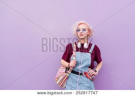 Portrait Of A Stylish Bright Young Girl With Headphones, Sunglasses And Colored Hair On A Purple Bac