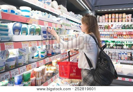 Young Girl With A Basket In Her Hands Chooses Cheese In The Milk Department Of The Supermarket. Woma