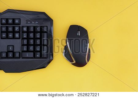 Workspace With A Keyboard And Mouse On A Yellow Background. Copyspace. Black Mouse, Keyboard Isolate