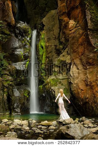 Beautiful Long Hair Blonde Woman In White Lace Dress Stands Under A Waterfall, In Azores Islands