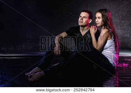 Couple Young Teens Together In Small Pool, Drops Of Water And Colored Light
