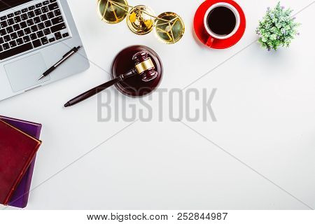 White Lawyer Desk With Laptop, Book, Pen, Cup Of Coffee, Judges Gavel And Law Symbols.justice And La