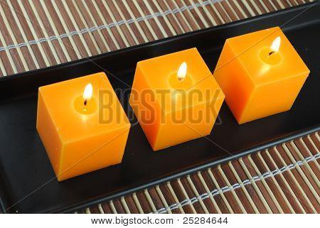 three orange candles in black dish on bamboo