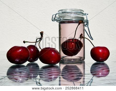 Wild Cherries And Glass Jar Of Sweet Cold Compote Against A High Key Background With Space For Your